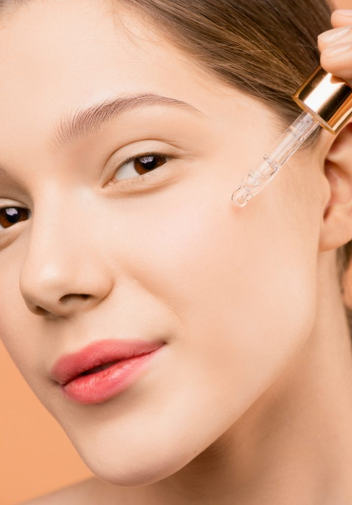 woman using facial serum with a dropper